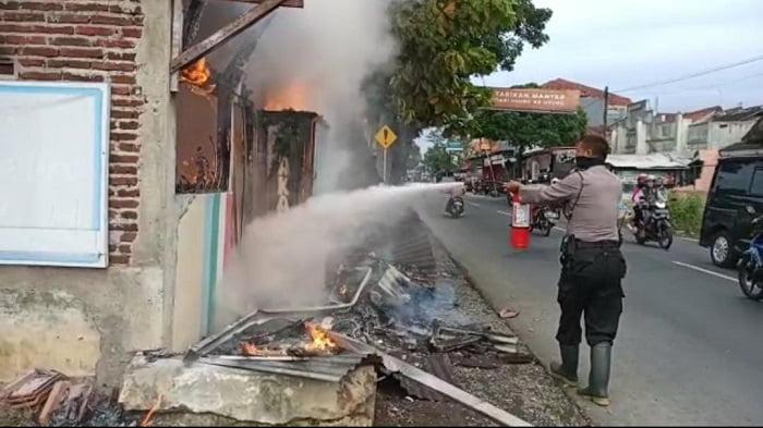 anggota polisi polsek padamara purbalingga saat bantu padamkan api kebakaran